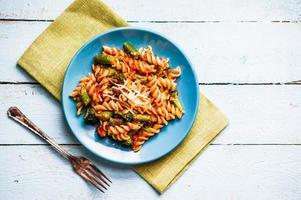 Nudeln mit Gemüse und Käse auf Holzhintergrund foto