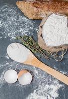 Brötchen oder französisches Baguette und Mehl auf Schwarz foto