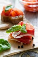Fleischscheibe und Tomatenbruschetta mit Basilikumblättern, Knoblauch foto