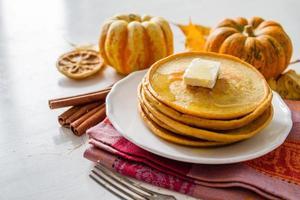 Kürbispfannkuchen auf weißem Teller mit Butter und Honig
