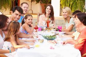 große Familiengruppe, die gemeinsam auf der Terrasse isst foto