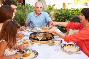 Familie mit mehreren Generationen, die gemeinsam auf der Terrasse essen foto