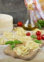frische hausgemachte Pasta Maschine Pasta, Basilikum, Tomaten auf einem Holz foto