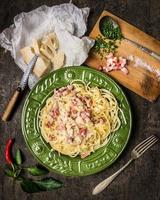 Pasta Carbonara in grünem Teller, Parmesan, Gewürzen und Gewürzen foto