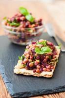 Bruschetta mit grünen Linsen, Avocado, Rüben und Erdnüssen foto