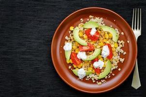 Salat mit Quinoa, roten Linsen, Mais, Avocado und Tomate foto