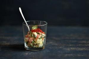 russischer Salat mit Lachs und rotem Kaviar auf blauer Oberfläche