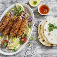 Hühnchen-Kebabs auf einem ovalen Teller und hausgemachte Tortilla