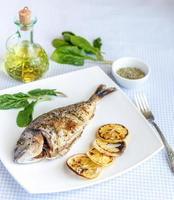 Gegrillter Dorada-Fisch mit Zitrone und Spinat foto