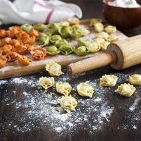 ungekochte Tortellini mit Käse auf einem Tisch foto