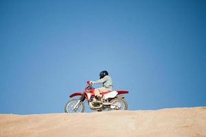 Mann, der Dirtbike auf Hügel reitet foto