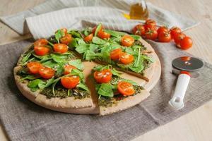 Pizza mit Pesto, Spinat und Kirschtomaten