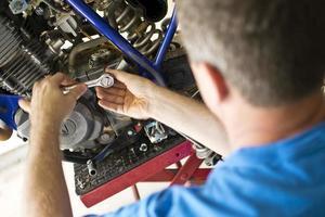 Mechaniker mit Ratsche zur Motorreparatur
