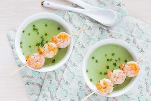 samtig grüne Sahnesuppe aus Brokkoli, Erbsen, Spinat, Garnelen foto
