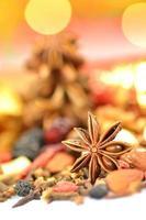 Weihnachtsgewürze, Nüsse, Kekse und getrocknete Früchte auf Bokeh-Hintergrund