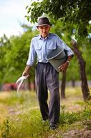 alter Bauer, der in einem Obstgarten düngt