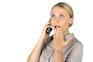 schockierte junge Frau, die am Handy spricht foto