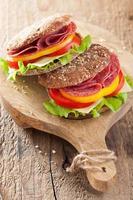 gesundes Sandwich mit Salami-Tomaten-Pfeffer und Salat foto
