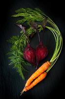 Rote Beete und Karotten auf schwarzer Schiefertafel