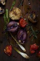Gegrillte Zwiebeln und Gemüse auf Schneidebrett foto