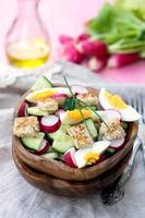 Salat mit Radieschen, Gurke, Eiern und Brotcroutons foto