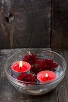 rote Kerzen und Blumen in einer Schüssel foto