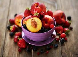 Pfirsiche und Beeren in der Schüssel auf Tischnahaufnahme foto