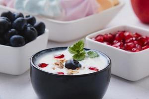 Joghurt mit Müsli, Blaubeeren und Granatapfel foto