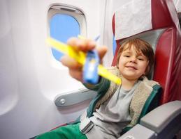 lächelnder Junge mit Spielzeugflugzeug, das auf Düsenflugzeug fliegt foto