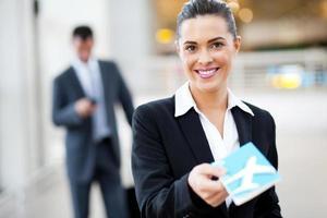 Geschäftsfrau übergibt Flugticket am Check-in-Schalter foto