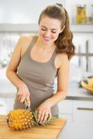 glückliche junge Frau, die Ananas schneidet