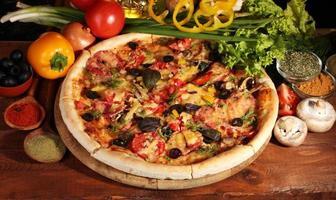 leckere Pizza, Gemüse und Gewürze auf Holztisch
