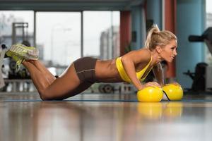 Frau, die Liegestütze auf gelben Bällen ausübt foto
