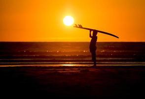 Mann mit Surfbrett im Sonnenuntergang am Strand