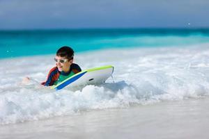 Junge schwimmt auf Boogie Board foto