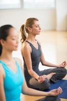 schöne Frau, die Yoga im Fitnessstudio praktiziert