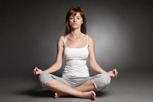 junge Frau, die Yoga gegen dunklen Hintergrund tut foto