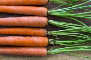 Karottenreihe auf Holzschneidebrett foto