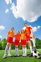 Kinder unterschiedlicher Größe mit Fußball in Reihe