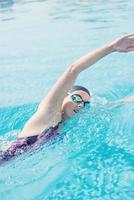 Frau in der Schutzbrille, die Frontkriechart schwimmt foto