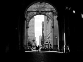 Paar unter dem städtischen Gebäudebogen - New York, Manhattan foto