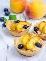 hausgemachte Törtchen mit Pfirsich und Blaubeeren