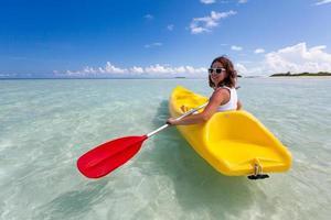 junge kaukasische Frau, die im Meer auf den Malediven Kajak fährt