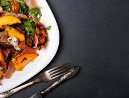 dunkles Artfoto des köstlichen Salats mit gegrillten Pfirsichen foto