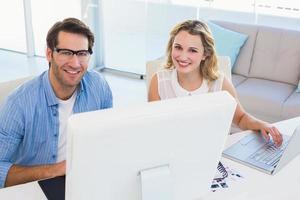 fröhliche Bildbearbeiter, die gemeinsam am Grafiktablett arbeiten foto