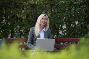 Geschäftsfrau im Park, der auf Bank sitzt und Laptop verwendet