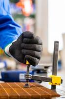 Werkstatthandwerker klemmt Metall auf Werkbank