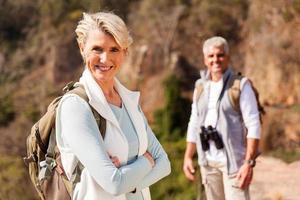 ältere weibliche Wandererin, die auf Berg steht foto