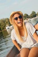 junge fröhliche Frau, die auf einem Boot genießt