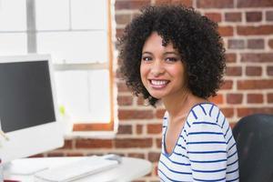 lächelnder weiblicher Bildbearbeiter, der Computer im Büro benutzt foto